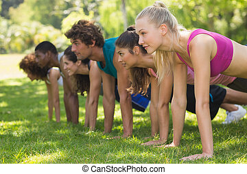 Side view of a group of fitness people doing push ups in the park