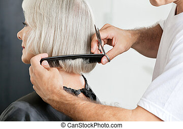 Closeup of male hairstylist measuring hair length before haircut in parlor