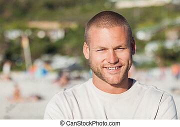 Handsome happy man posing on the beach