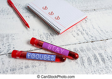 Handwriting text Stay Focused. Concept meaning Be attentive Concentrate Prioritize the task Avoid distractions Extracted blood sample vial with medical accessories ready for examination.