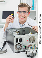 Happy computer engineer working on broken device