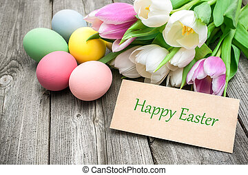 Easter eggs and tulips with a tag on wooden background