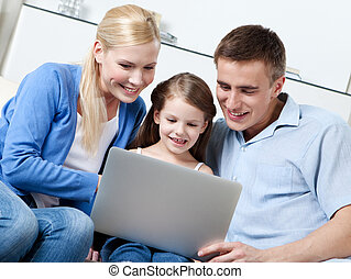 Happy family sit on the sofa with laptop