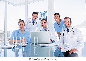 Happy medical team using laptop together