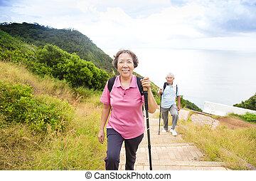 happy senior couple hiking on the mountain park