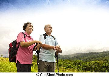 happy senior couple hiking on the mountain