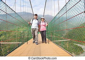 happy senior couple walking on the bridge in the nature park