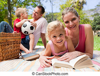 Happy young family enjoying a picnic in a park