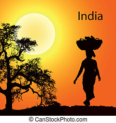 Indian women with basket on the head at the sunsetr
