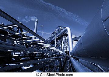 industrial pipelines on pipe-bridge against sky in blue tone