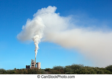 Smoke from an industrial plant drifting in the wind against a blue sky