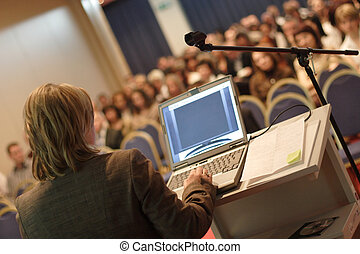 Business woman at podium with laptop computer lecturing audience in auditorium