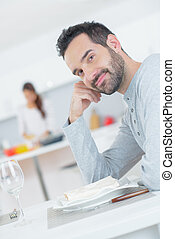 Man sat at table, waiting for meal