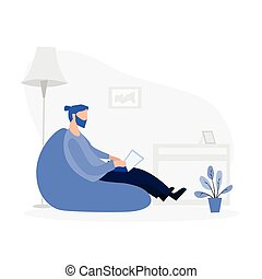 Man sitting on the puff armchair and working on laptop at home