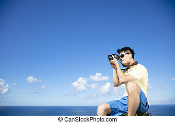 Man taking photo of ocean view sitting on top of the rock