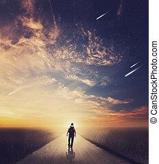 Man walking down road at sunset