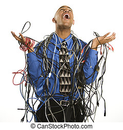 African American businessman wrapped in computer cables looking up with exasperation.