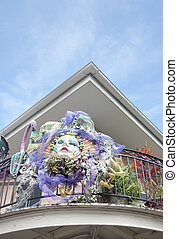 Mardi Gras mask on a balcony of a building in New Orleans French Quarter