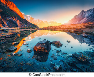 Mountains with illuminated peaks, stones in mountain lake at sunset