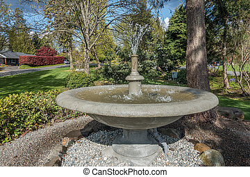 A cement fountain gushes in Normandy Park Washington in the Pacific Northwest.