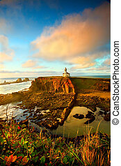 Portrait of the Cape Arago lighthouse along the Oregon coast at sunset during low tide.