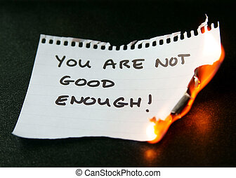 burning piece of paper saying you are not good enough