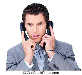 Pensive businessman tangle up in phone wires