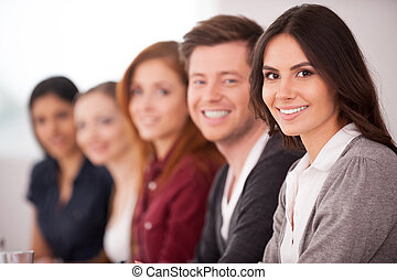 People at the seminar. Attractive young woman smiling at camera while other people sitting behind her in a row