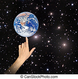 Planet earth on finger. Elements of this image furnished by NASA