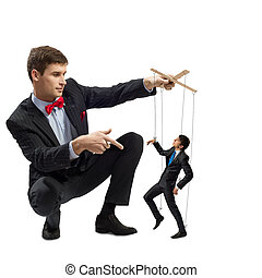 puppeteer holds the puppet business man on the ropes