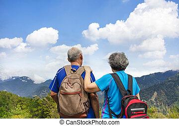 Rear view  Senior  couple hiking on the mountain