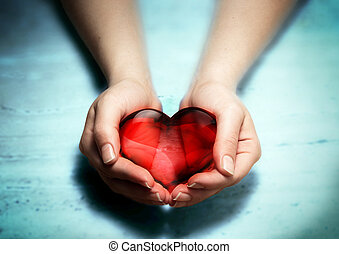 Red glass heart in woman hands