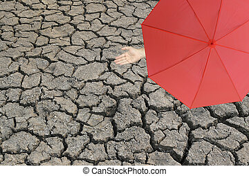 Red umbrella and a hand of man standing on cracked earth and hand protruding outside the radius to determine whether it rains or not.