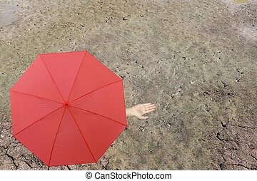 Red umbrella and a hand of man standing on soil dry pond and hand protruding outside the radius to determine whether it rains or not.