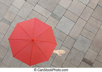Red umbrella and a hand of man standing on stone floor and hand protruding outside the radius to determine whether it rains or not.