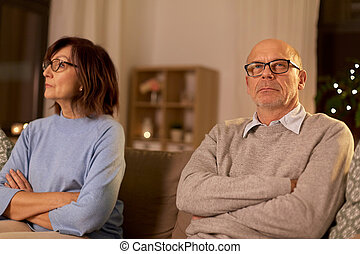 unhappy senior couple sitting on sofa at home