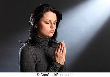 Afternoon shaft of light streams into room as beautiful young caucasian woman with eyes closed, has a quiet religious moment deep in prayer, wearing crucifix necklace.