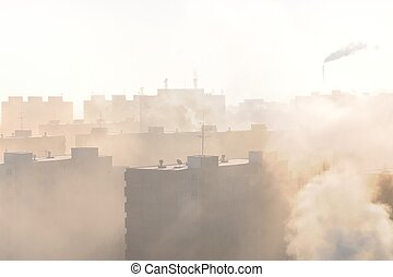 Residential area in fog and smog with chimney in background