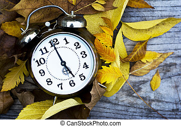 Retro metal clock standing on wooden table with leaves laying around