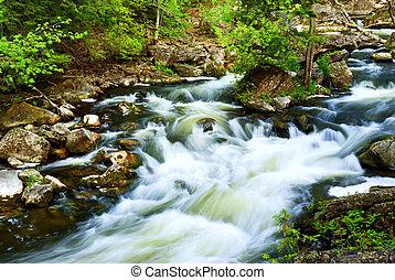 Water rushing among rocks in river rapids in Ontario Canada