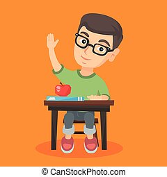 Schoolboy sitting at the desk with raised hand.
