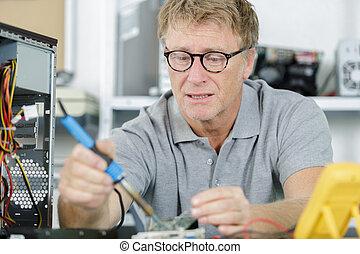 senior computer engineer working on broken console