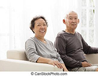 senior couple sitting close together on the sofa