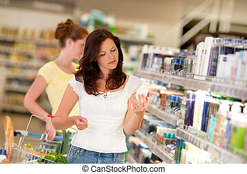 Brown hair woman in cosmetics department holding bottle of shampoo