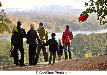 Silhouette of family admiring an autumn decline above the river
