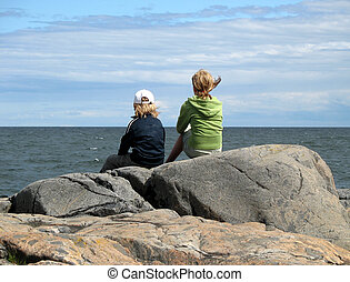 Sitting boy and girl by the ocean