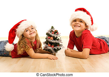 Happy kids with small christmas tree, laying on the floor wearing santa hats - isolated