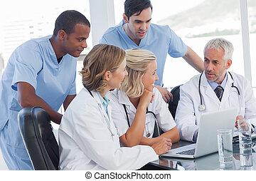 Smiling medical team using laptop