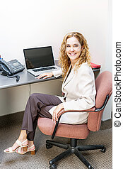 Smiling woman sitting at office desk