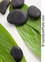 Spa massage stones on bamboo leaves